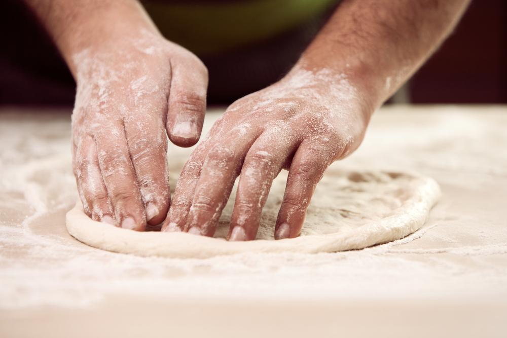 Liebevolles Ausrollen des Pizzateigs
